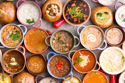 Fotografie, Tablou  Variety of Garnished Soups in Colorful Bowls