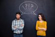 Frowning couple standing after argument over chalkboard background