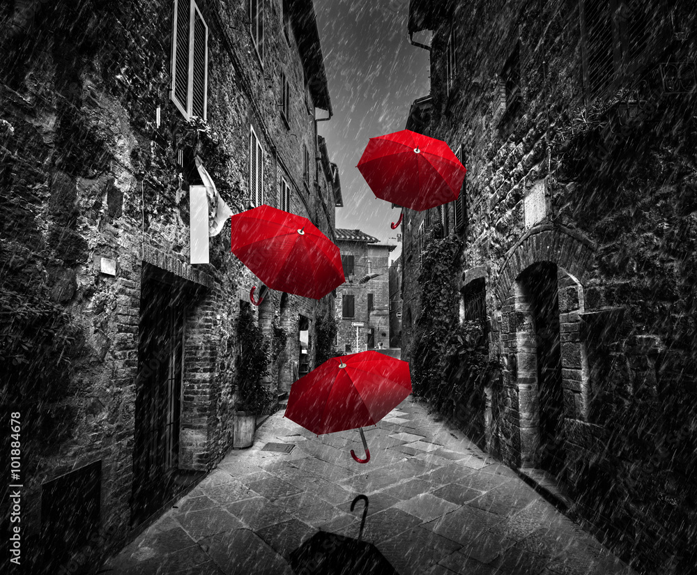 Fototapeta Umrbellas flying with wind and rain on dark street in an old Italian town in Tuscany, Italy