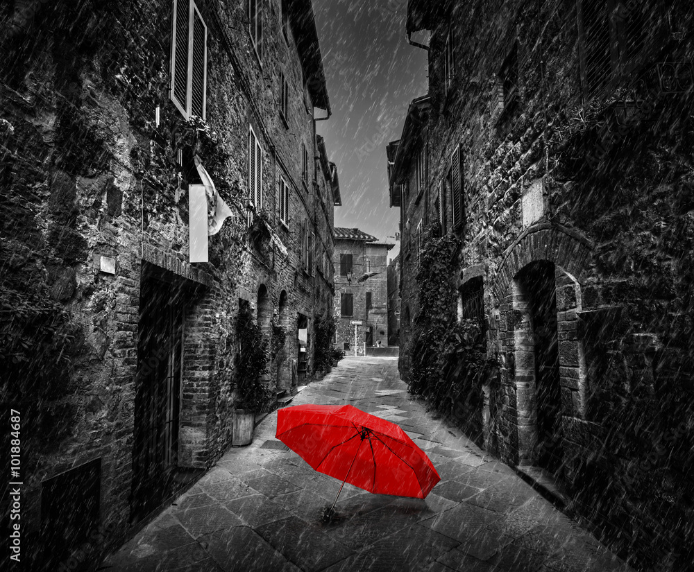 Fototapeta Umbrella on dark street in an old Italian town in Tuscany, Italy. Raining.