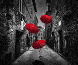 Fototapeta Uliczki - Umrbellas flying with wind and rain on dark street in an old Italian town in Tuscany, Italy
