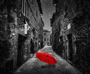 Parasol na ciemnej ulicie w starym Włoskim miasteczku w Tuscany, Włochy. Pada.