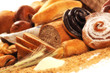 Composition with bread and rolls in wicker basket, combination of sweet pastries for bakery or market with wheat