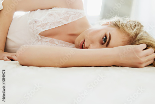 Fotografie, Tablou  Portrait of a beautiful blonde girl lying on a white bed