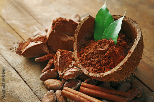 Fotografering  Bowl with aromatic cocoa powder and green leaf on wooden background, close up