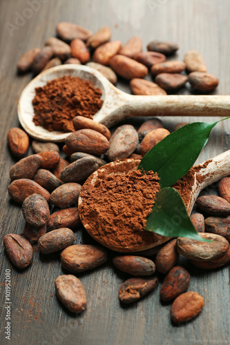 Photo  Spoon with aromatic cocoa and chocolate on wooden background, close up