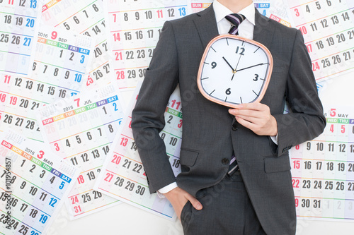 Valokuva  カレンダーの前で時計を持っているビジネスマン