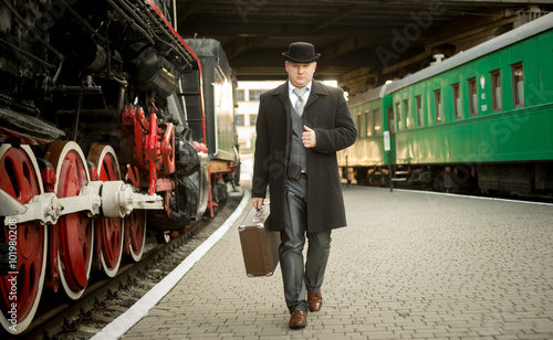 Photographie  man in retro suit with suitcase walking on the train platform