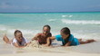 young family with two girls resting at beach in sunny day.mother and her two daughters lie on a tropical beach and playing with sand, talking.Travel concept.Family,summer vacation