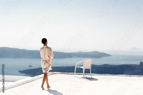 Fotografie, Obraz  Beautiful sexy brunette bride in robe walking on hotel roof with