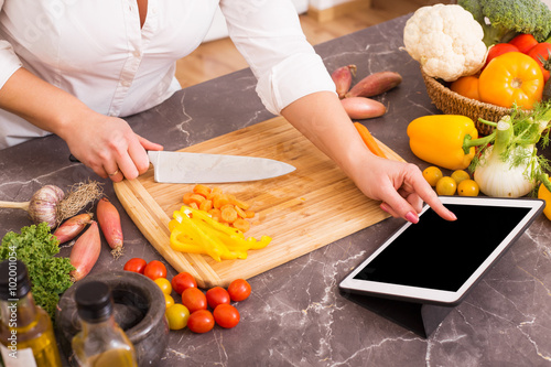 Foto op Canvas Koken Woman using tablet for cooking