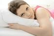 Frau liegt erholt im Bett nach Schlaf, Ausschlafen oder Mittagsschlaf