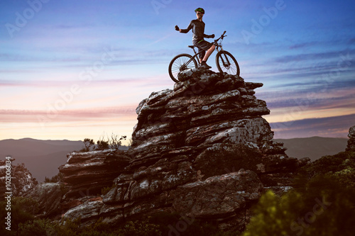 Poster  Happy biker on a big rock