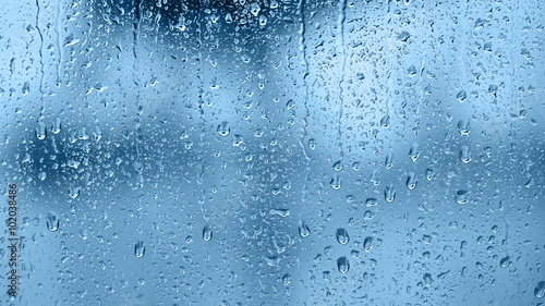 Raindrops on the window. Blue tone