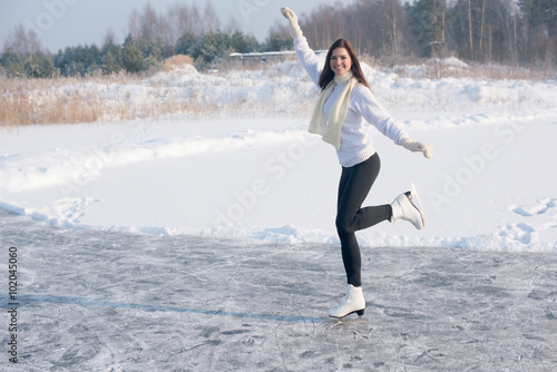 Fotobehang Wintersporten young Figure skating woman at the frozen lake in the winter