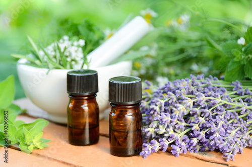 Photo  essential oils with herbs in garden spa