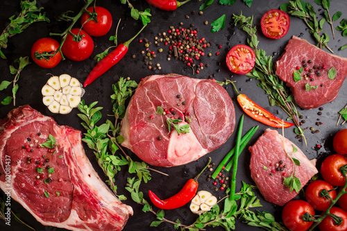 Fotografia, Obraz  Raw meat steaks on a dark background ready to roasting
