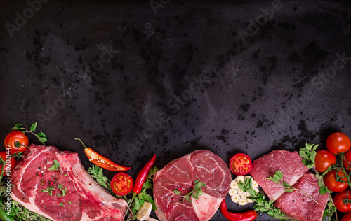 Photo Stands Meat Raw meat steaks on a dark background ready to roasting