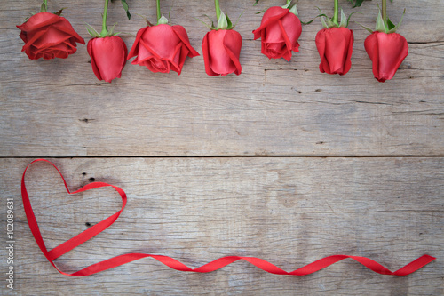 Keuken foto achterwand Roses Valentines day background with red rose and ribbon on wooden.