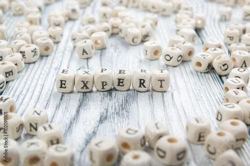 Láminas  text of EXPERT on wood cubes. Wooden ABC