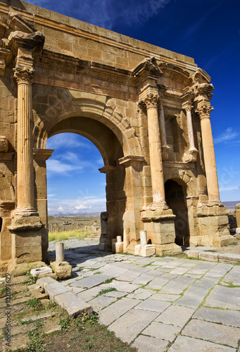 Poster Algérie Algeria. Timgad (ancient Thamugadi or Thamugas). Triumphal arch, called Trajan's Arch (Corinthian order with three arches) and paving stones of Decumanus Maximus street