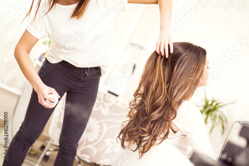 Foto auf Gartenposter Friseur Hairdresser spraying his customer's hair