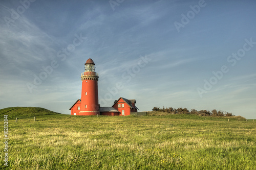 Fotografia beautiful red Lighthouse Bovbjerg Fyr with green grass and blue sky, HDR, Danish
