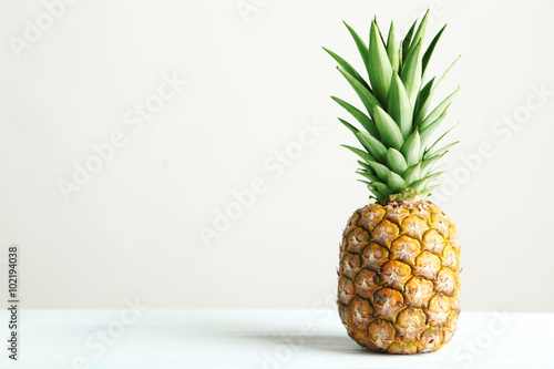 Fotografia Ripe pineapple on a white wooden table