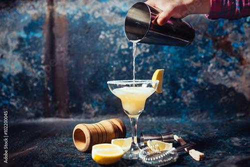 Cuadros en Lienzo Bartender pouring fresh lime margarita in fancy glass at restaurant