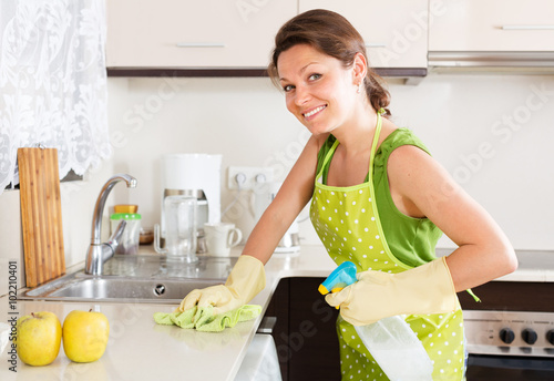 Fotografía  Smiling  woman cleaning furniture in kitchen