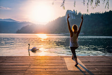 Sun Salute Yoga. Young Woman Doing Yoga By The Lake At Sunset, Swan Passing By