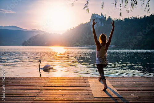 Staande foto School de yoga Sun Salute Yoga. Young woman doing yoga by the lake at sunset, swan passing by
