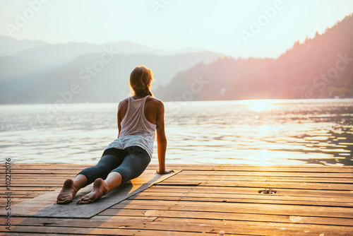 In de dag School de yoga Yoga sun salute. Young woman doing yoga by the lake at sunset