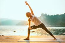 Sun Salutation Yoga. Young Woman Doing Yoga By The Lake, Sunset Time, Toned Image