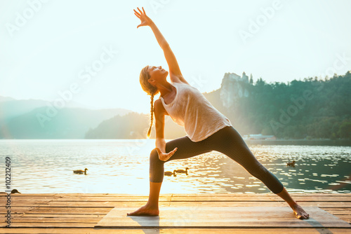Staande foto School de yoga Sun Salutation Yoga. Young woman doing yoga by the lake, sunset time, toned image