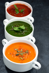 Fototapetaassortment of fresh vegetable soup on dark background, vertical
