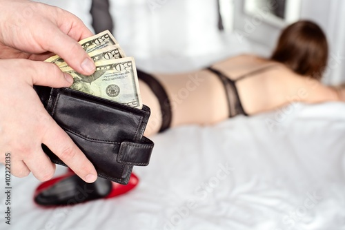 Fotomural The man pays a prostitute with american money dollar