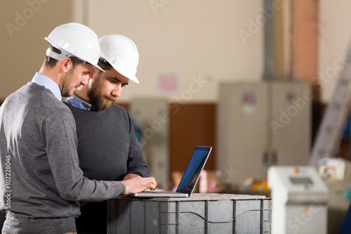 Two businessman working with laptop in factory