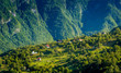 Village in the mountains. Rural houses in the hills somewhere between the high mountains in Montenegro. Summer landscape in evening warm light.