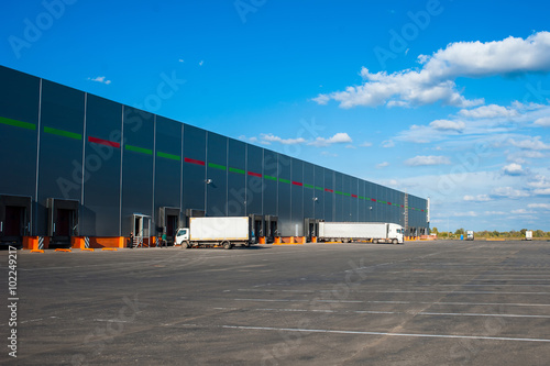 Staande foto Industrial geb. Trucks at big industrial warehouse building