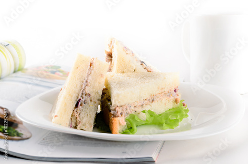 Photographie  Breakfast of creamy tuna sandwiches with cup of tea and a journa