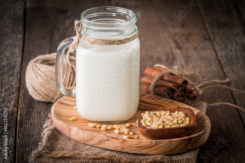 Fotobehang cedar milk in a glass jar and pine nuts