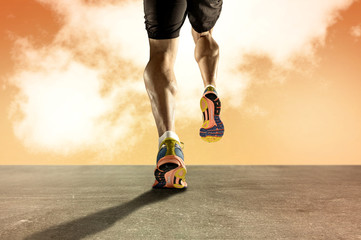 Fototapeta Bieganie strong athletic legs with ripped calf muscle of young sport man running on grunge asphalt road at orange sunset sky