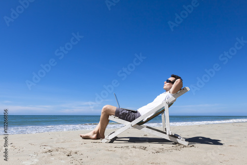 Foto op Aluminium Ontspanning Freelancer resting on sunny tropical beach with sunglasses