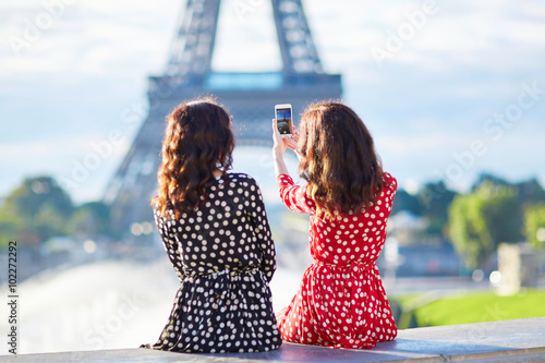 Photo  Beautiful twin sisters taking selfie in front of Eiffel Tower