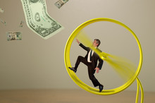 A Businessman Is Running On A Hamster Wheel Fruitlessly Chasing A Dollar Bill Hanging Just Outside His Reach Representing Many Financial Business Concepts