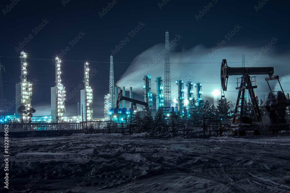 Fototapety, obrazy: Oil rigs and brightly lit industrial site at night.