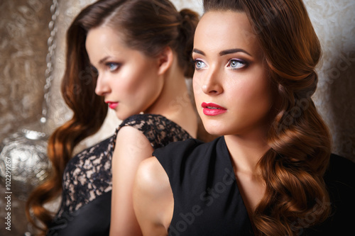 Photo  Portrait of beautiful twins young women in gorgeous evening dresses