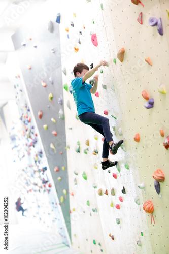 Foto op Canvas Alpinisme Bambino che scala una parete per arrampicata
