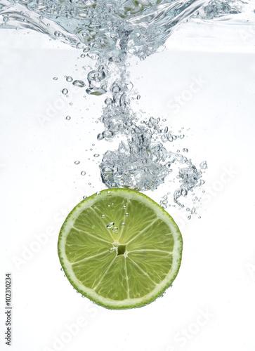limonka-spadajaca-w-wodzie-na-bialym-tle